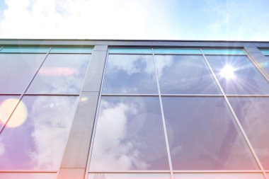 Modern office building detail, glass surface with sunlight