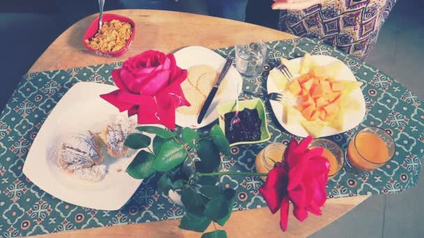 Hands taking breakfast food from table with flowers slow motion
