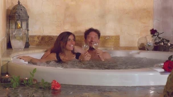 Šťastný pár v lásce opékání s vínem uvnitř vířivky v lázních hotelu v retro stylu dovolené