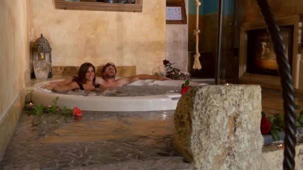 Happy couple laughing having fun in whirlpool in spa in vacation