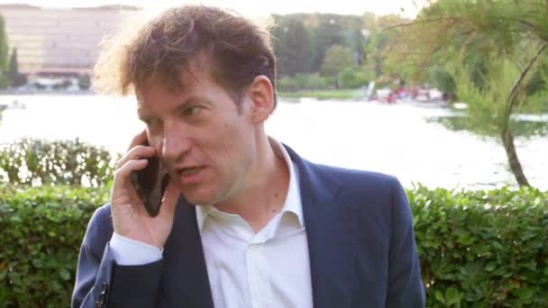 Unhappy business man on the phone getting angry in city at sunset in front of lake in park slow motion