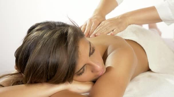 Žena dostává jemnou masáž ramen v lázeňském zpomaleném pohybu