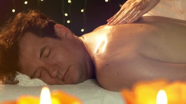 Boldog mosolygós férfi, aki élvezi masszázs közben a szálloda pihentető