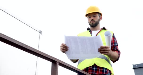 architect in helmet and safety vest checking blueprints
