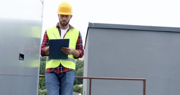 male architect in safety vest and hardhat making notes in notepad