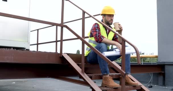 mužské architekt v přilbu a bezpečnostní vestu pití kávy během přestávky na kávu