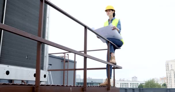 female architect in helmet and safety vest with blueprints standing on location