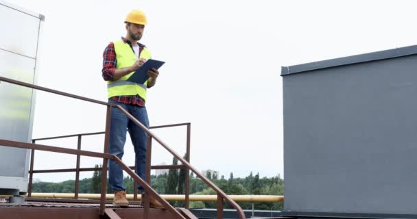architect in helmet and safety vest making notes in notepad