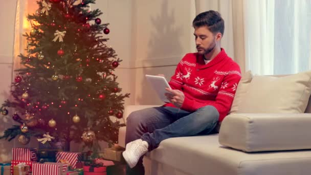 handsome young man sitting on couch and using tablet in christmas decorated living room
