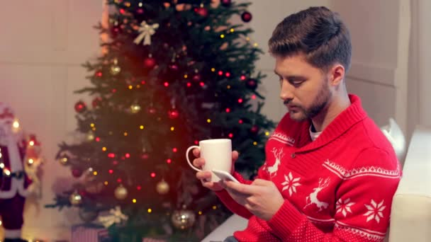 handsome young man sitting on couch with cup of coffee and using smartphone in christmas decorated living room