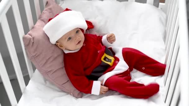 roztomilé usměvavé dítě v kostýmu santa leží na polštáři v postýlce doma, vánoční koncepce