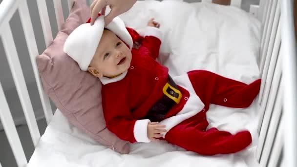 matka dotýká čelem usměvavé rozkošné dítě v kostýmu santa v postýlce doma, vánoční koncepce