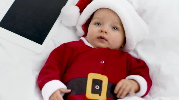 Verärgertes entzückendes Baby im Weihnachtsmannkostüm liegend mit Tablet in der Krippe zu Hause, Weihnachtskonzept