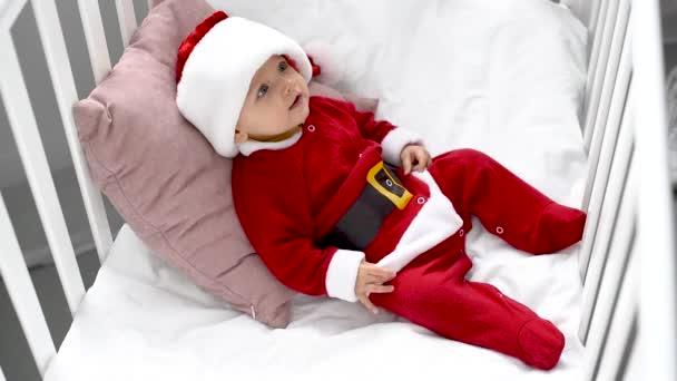 roztomilé usměvavé dítě v kostýmu santa sedí v postýlce doma, vánoční koncepce