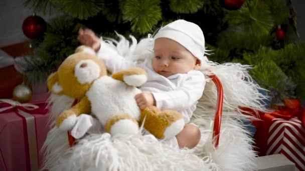 entzückendes Baby spielt mit Teddybär auf Stuhl in der Nähe von Weihnachtsbaum zu Hause