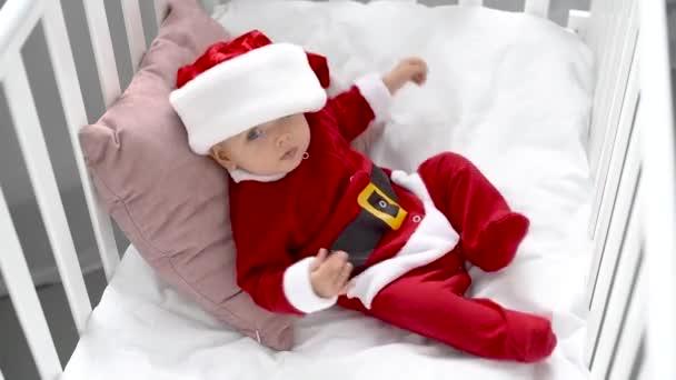 Mothe oprava klobouk na rozkošné dítě v kostýmu santa v postýlce doma, vánoční koncepce