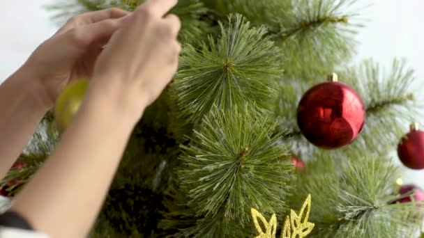 cropped view of woman decorating christmas tree with balls at home