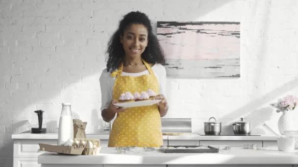 lächelnde junge afrikanisch-amerikanische Frau in Schürze hält Teller und zeigt Cupcakes in der Küche