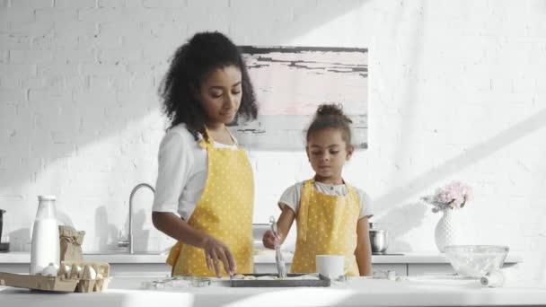 africká americká žena učí svou malou dcerou v zástěře kartáčování těsta na zásobník v kuchyni