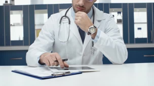 male doctor in white coat using digital tablet and writing diagnosis in clinic
