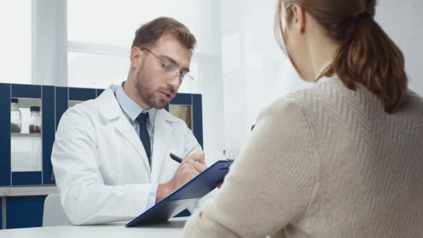 male doctor writing diagnosis and consulting woman in clinic
