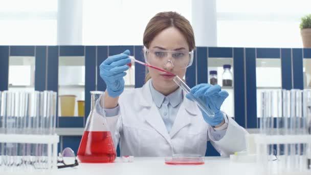 Wissenschaftlerin in Schutzbrille steckt bei Experiment im Labor rote Flüssigkeit in Röhre