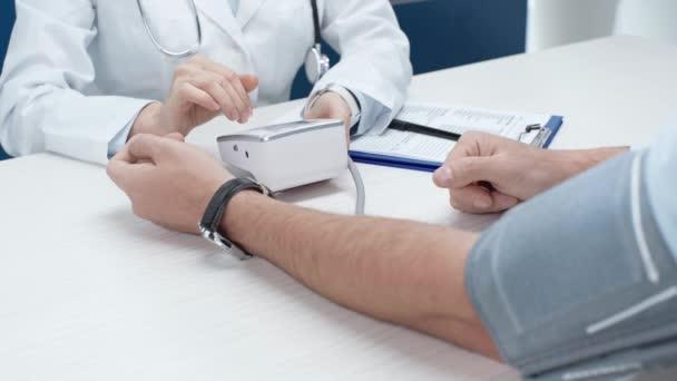 oříznutý pohled lékařka měření krevního tlaku člověka s tonometr v klinice