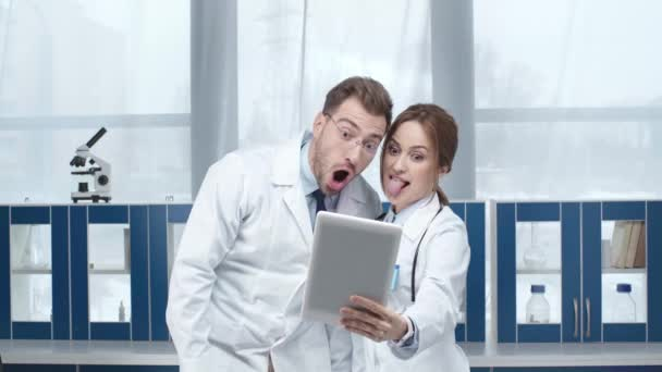 female and male doctors showing various face expressions while taking selfie on digital tablet in clinic