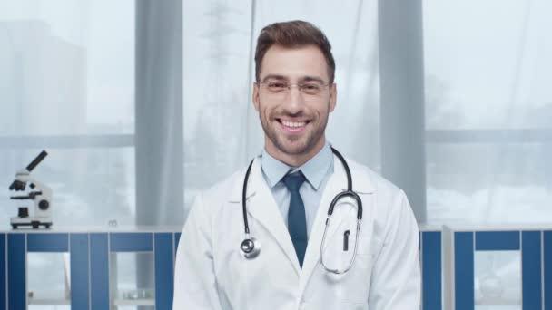pohledný muž lékař v bílém plášti, s úsměvem a při pohledu na fotoaparát v klinice