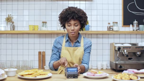 szép afro-amerikai női pénztár használ hitelkártya és terminál-kávézóban, látszó-on fényképezőgép, és mosolyogva a pénz alá a háttérben