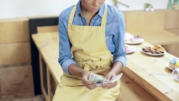 schöne afrikanisch-amerikanische Kassiererin, die im Café Geld zählt, lächelt und in die Kamera schaut