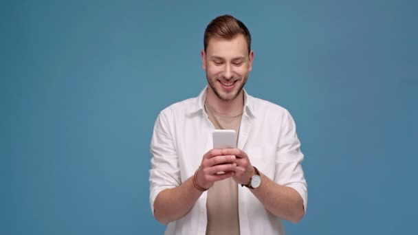 handsome man smiling and using smartphone isolated on blue with copy space