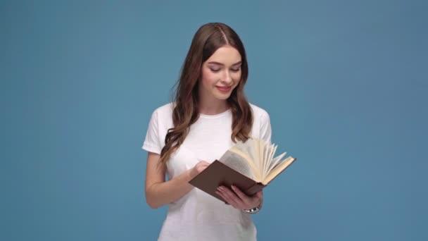 mosolygó lány fordult az oldalak és elszigetelt kék könyv olvasó beautifu