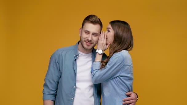 krásná dívka říct tajemství na překvapeného muže izolované na žluté