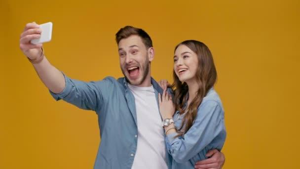 krásný šťastný pár při selfie na smartphone, Vypláznutí jazyka a ukazuje míru ve znamení izolované na žluté