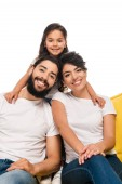 happy latin parents smiling while sitting on sofa near daughter isolated on white