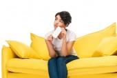 triste donna latina tenendo smartphone mentre seduto sul divano isolato su bianco