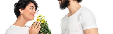 panoramic shot of cheerful latin man giving flowers to attractive woman isolated on white