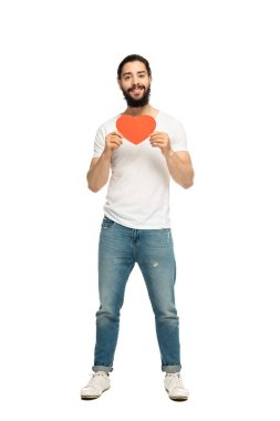 bearded latin man holding red heart-shape carton and smiling isolated on white