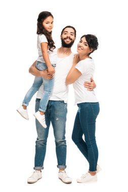 happy latin man holding in arms cute daughter while standing with wife isolated on white