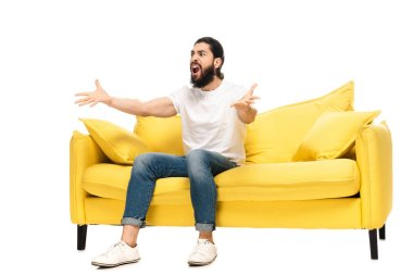 bearded latin man watching championship while sitting on sofa and gesturing isolated on white