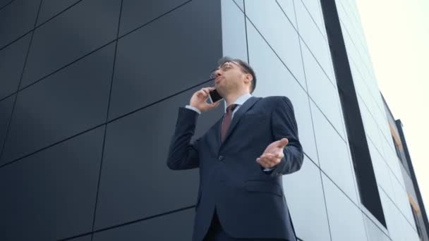 low angle view of businessman using smartphone, gesturing and smiling near building