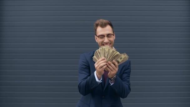 obchodník počítá peníze, usmívá se a odhazuje dolarové bankovky