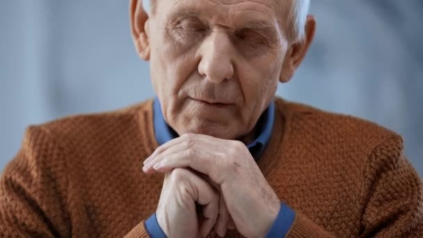 selektivní zaostření staršího muže se zaťatými dlaněmi a zavřenými oči, otvírající oči a pohled na kameru