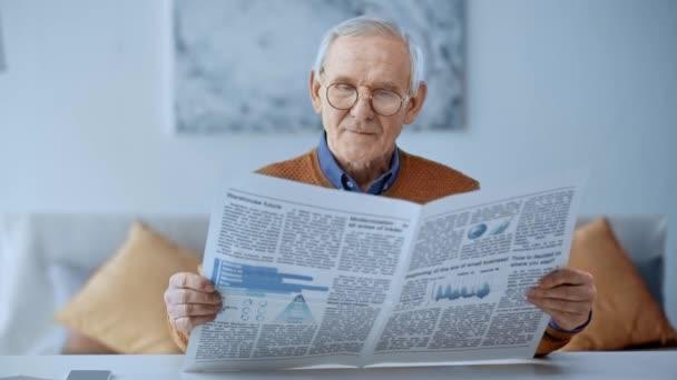selektivní zaměření šťastného muže v důchodu sedícího na pohovce a čtení novin doma