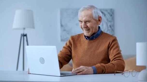 válogatós összpontosít-ból boldog nyugdíjas ember birtoklás video hív és integetett odaad rövid idő látszó-on laptop otthon