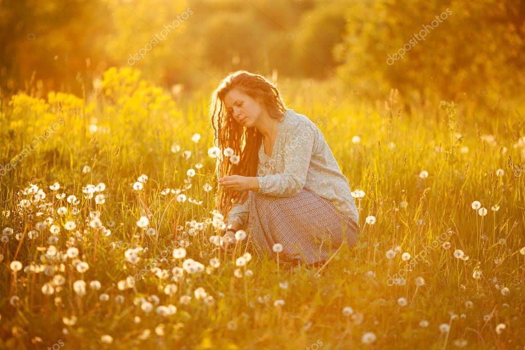 A girl with dreadlocks tearing dandelions in the middle of the field
