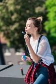 Fotografie atraktivní mladá žena foukačkou bublina na střeše