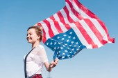 happy young woman holding united states flag against blue sky, independence day concept