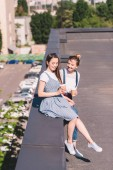 Fotografie high angle view of young female friends with paper cups of coffee at rooftop